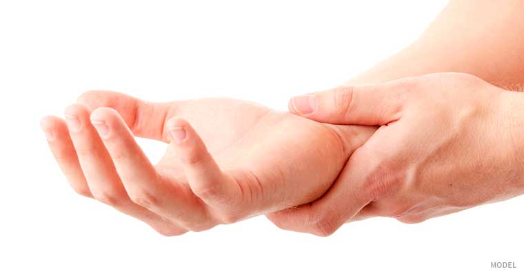 Person holding wrist, palm up